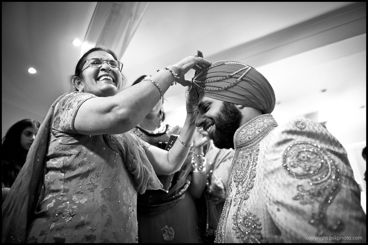 A big part of any wedding is the bride and groom getting ready on the big day. Here, a Punjabi Sikh man is helped in decorating his turban by a relative while close members of the family look on.  This picture was taken in London.