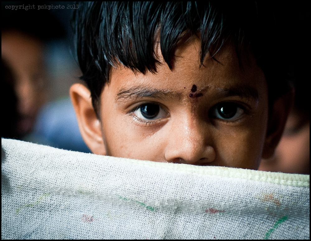 A small child peers over a chalk board cloth, Hyderabad, 2013