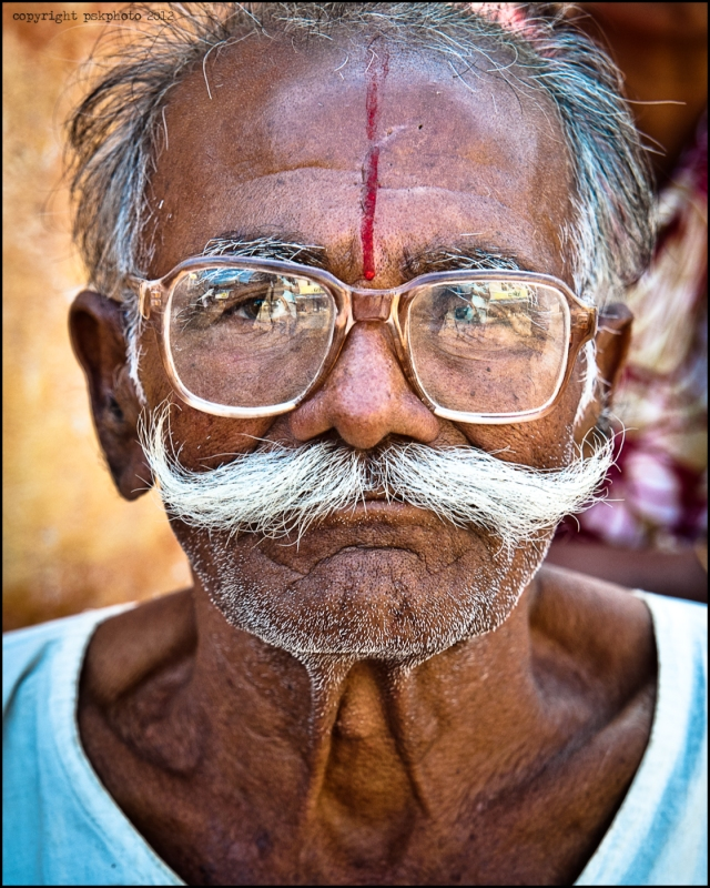 An ex-military man sitting by the street outside his home watching the world go by, poses happily for a picture. Hyderabad, India, 2013