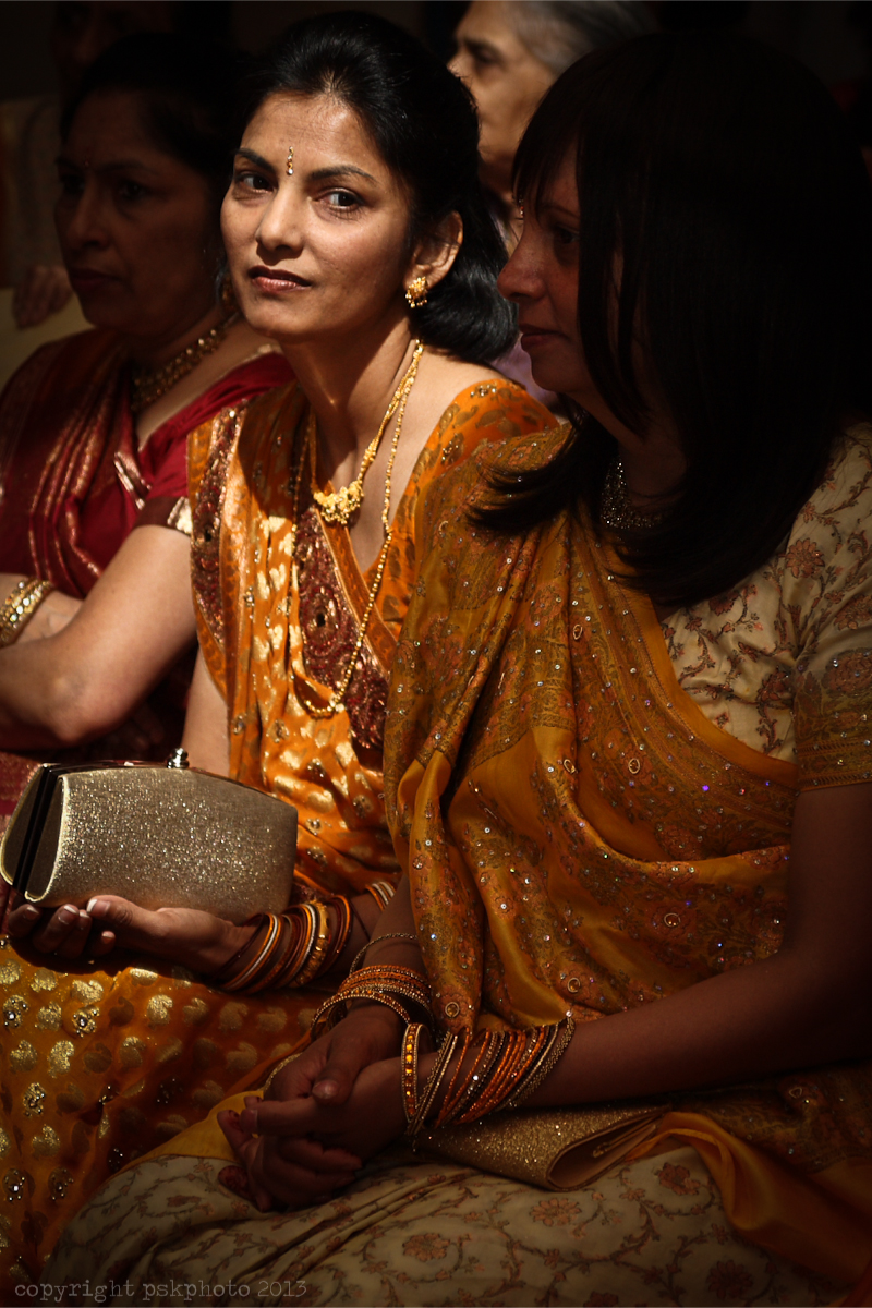 Sitting thoughtfully and fortunately for me, in beautiful light, a wedding guest waits for the arrival of the bride. During long Hindu wedding ceremonies, the seated guests regularly move between watching the proceedings and eating and socialising at a buffet. This very beautiful wedding went on for around three hours. London, 2012