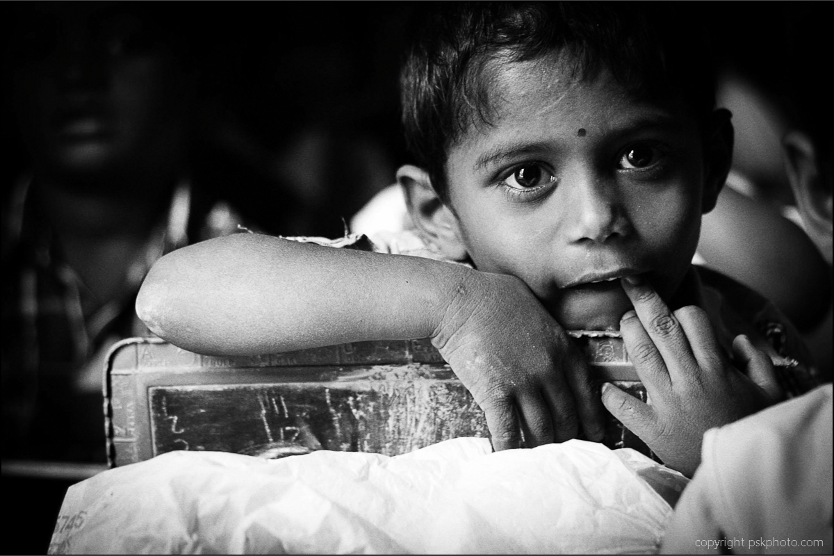 After a long day in the classroom, a little boy sits patiently waiting for the school mistress to finish her lesson. Children of a similar age in western schools would be more engaged in playing activities but here, ABC and 123 rule. Hyderabad, India, 2013