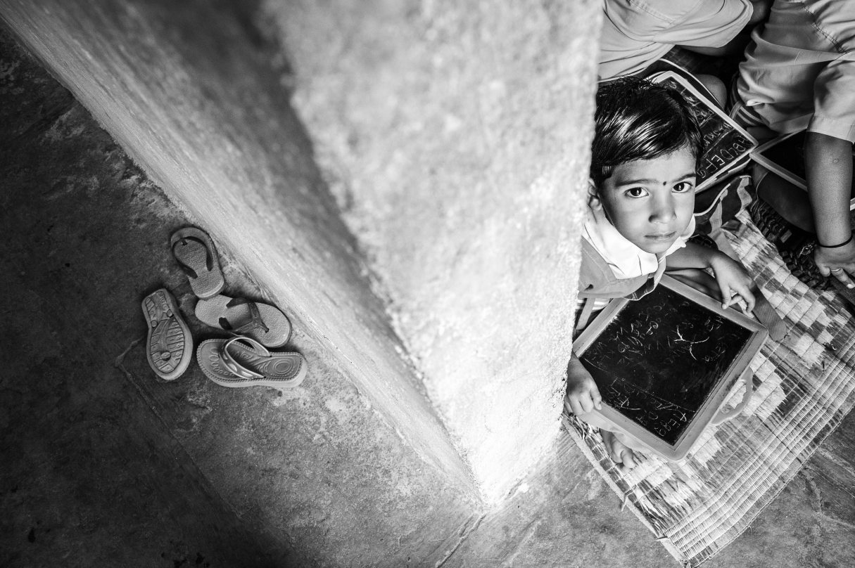 A small girl sits with slate in hand waiting for class to begin, MSF School, Hyderabad, 2013