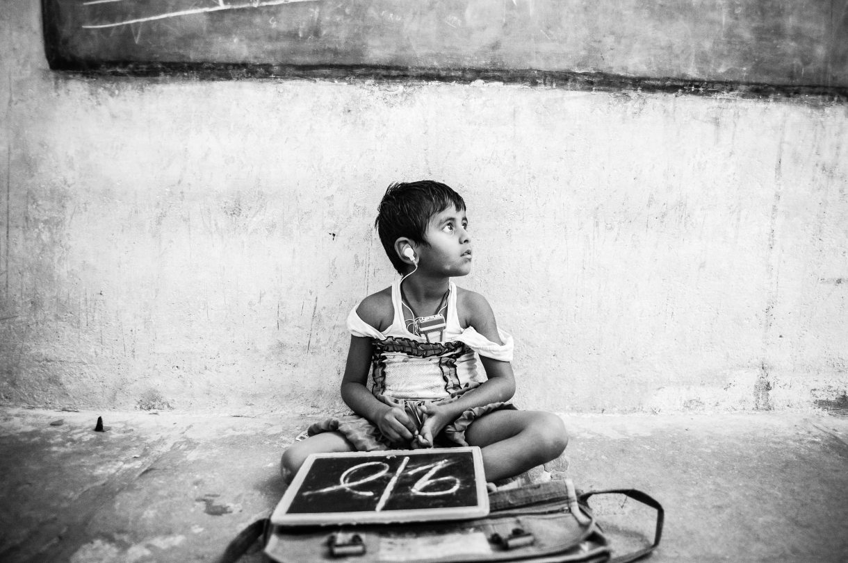 A small girl with hearing difficulties sits on the floor in class, Hyderabad, 2013