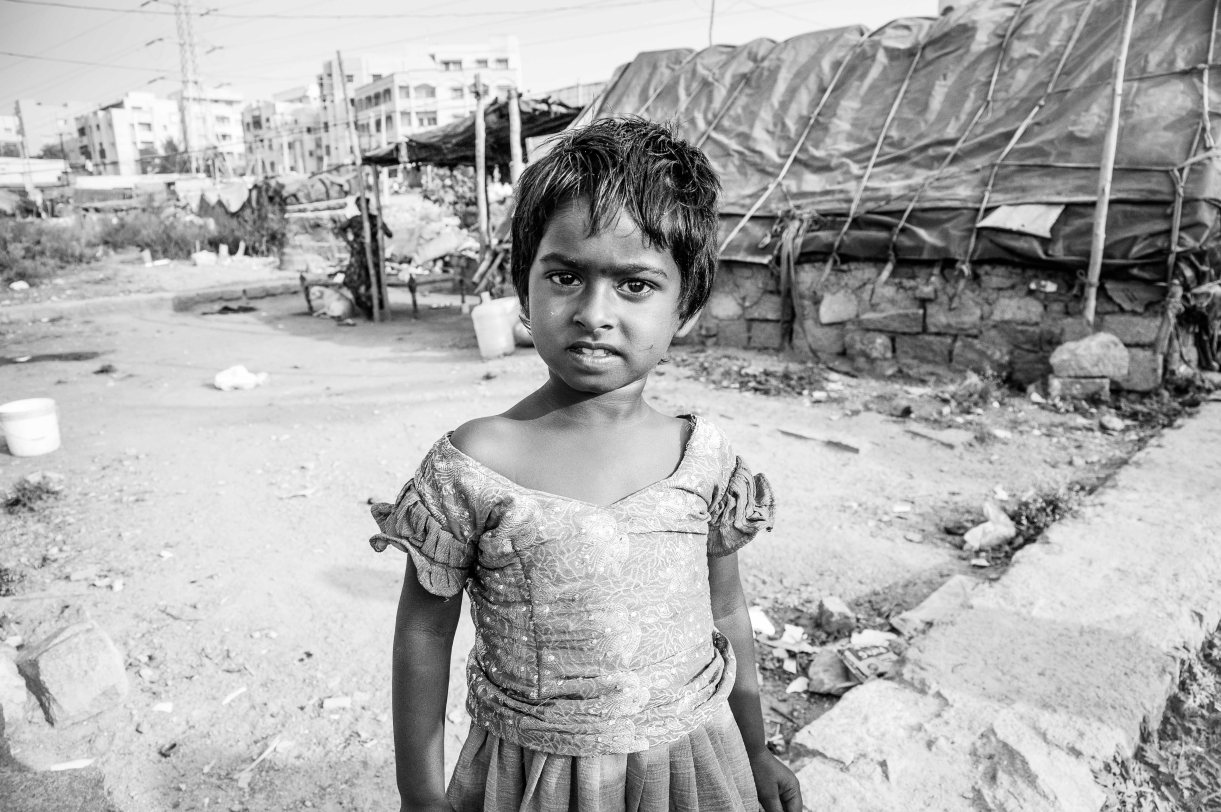A small slum child outside her shelter, Hyderabad, 2014