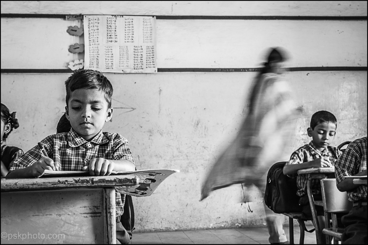 Schoolteacher keeping an eye on pupils, IDPL School, India, 2014