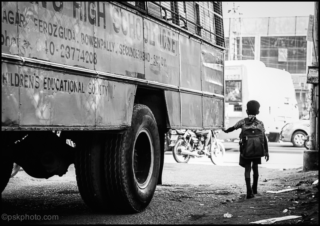School boy stepping carefully into the main road, Hyderabad, 2014