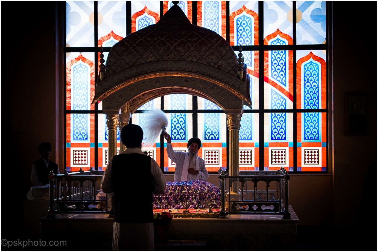 The Sikh holy book, the Guru Granth Sahib, is revered as the final living Guru. Here it is seen watched over by priests at Havelock Road Gurudwara in West London, 2014
