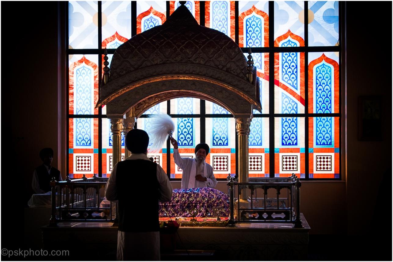 The Sikh holy book, the Guru Granth Sahib, is revered as the final living Guru. Here it is seen watched over by priests at Havelock Road Gurudwara in West London, 2014
