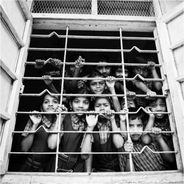 Small children peering out from a class room, IDPL School, India 2014