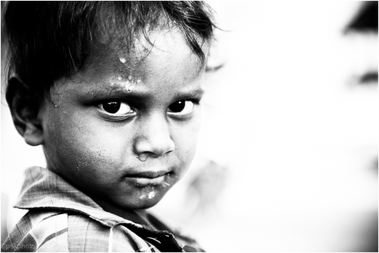 A small boy glances back across a dusty street in Telangana, India. He'd noticed me taking pictures and was waiting for me to notice him. Once I did, he fixed his gaze with great composure.