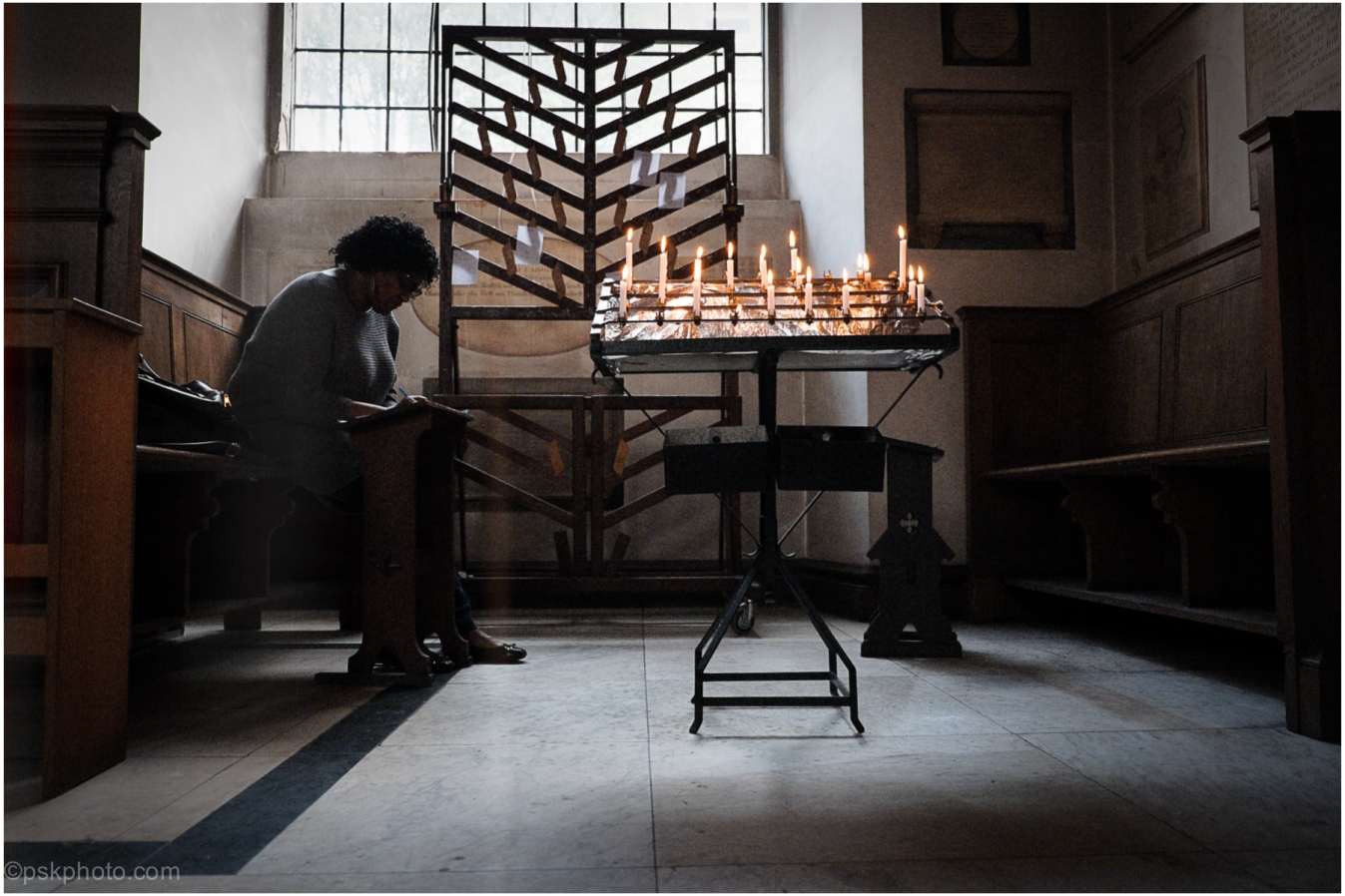 A lady sits quietly writing prayers for her family back in Lagos. She told me that she will clip the prayers onto the board provided and light a candle. St James's Church, Piccadilly, also known as St James's Church, Westminster and as St James-in-the-Fields,