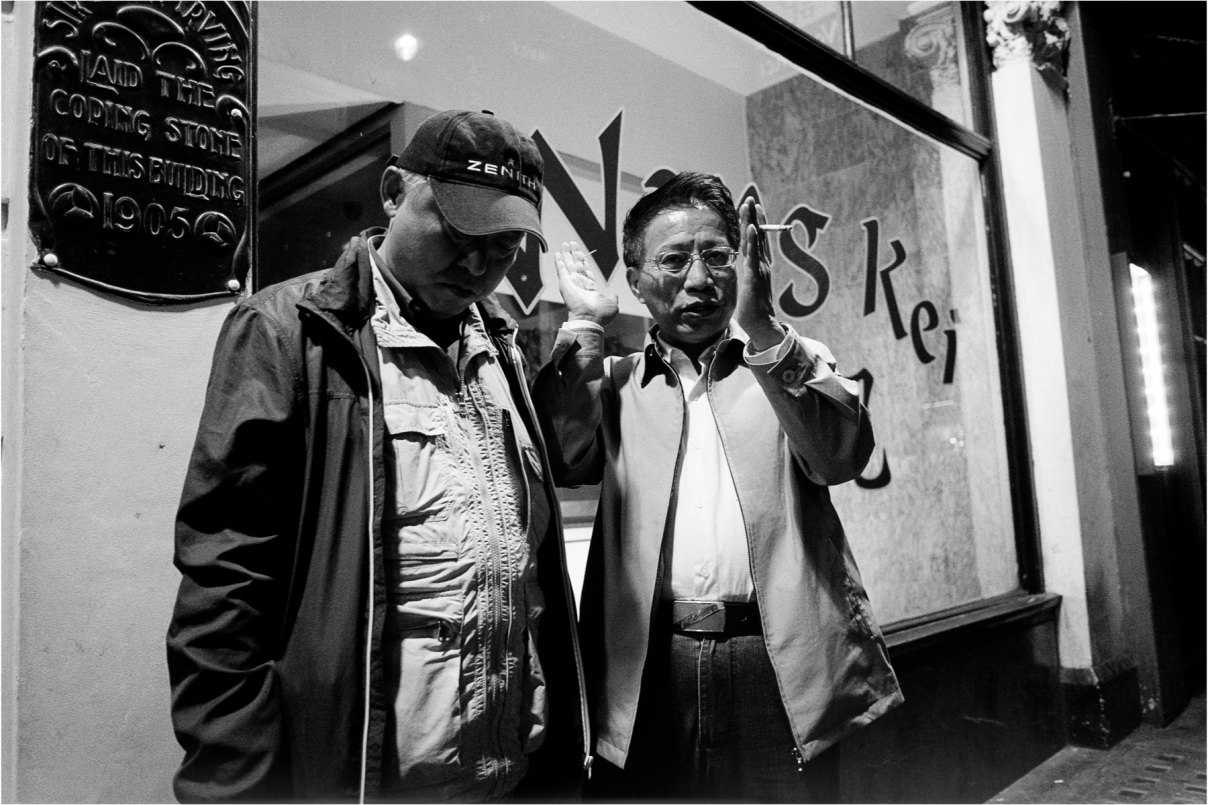 """Outside Wong Kei in Wardour Street London, famously, the rudest restaurant in Chinatown. One trip adviser reviewer says: """"poor service, but thats what makes this place so special""""  Brilliant! I have been using a new and very small Fuji lens which has quite a wide angle (26mm in 'full frame' terms) so I am really very close here. Still, these guys seem fairly unconcerned and despite the candid feel, they are perfectly camera aware!"""